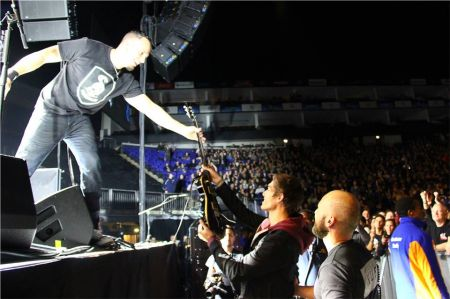 Alter Bridge's Mark Tremonti hands a lucky fan his guitar following their concert at the O2 Arena in London.