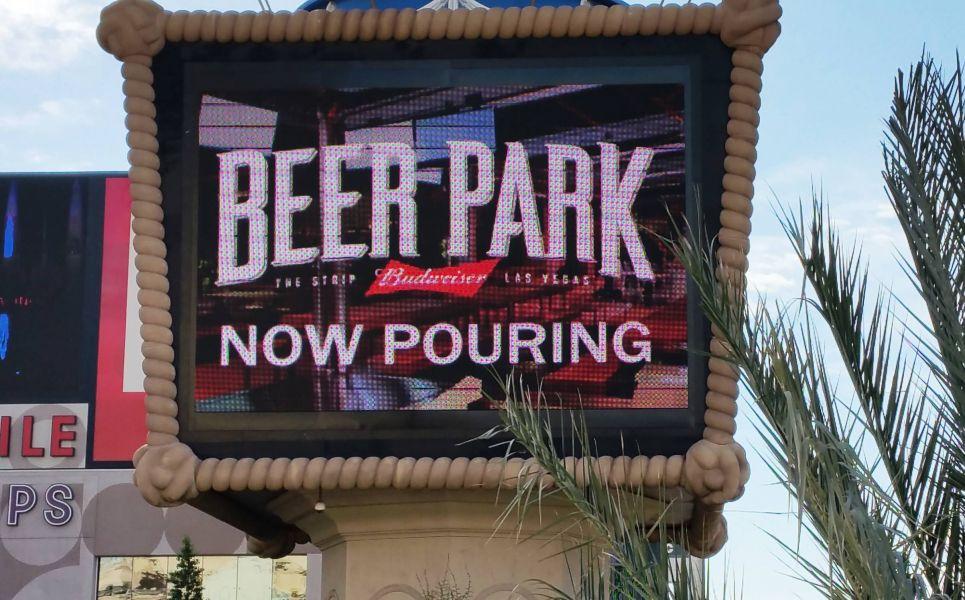 """Beer Park pylon sign announces """"now pouring"""""""